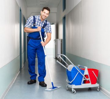 Happy Male cleaner with cleaning equipment's mopping floor