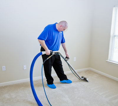 male cleaner performing Office Cleaning using vacuum clean