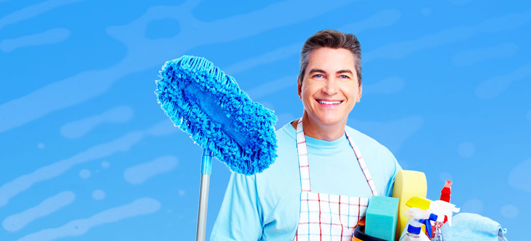 Smiling Male Cleaner with mop and cleaning equipments