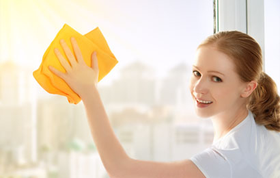 Smiling Young female cleaner wiping glass